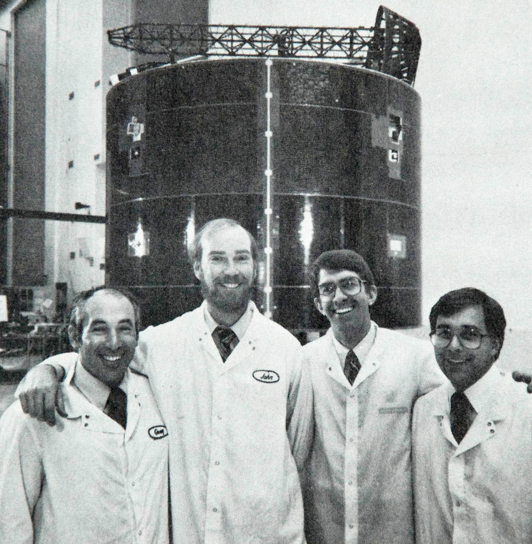 Payload Specialists Greg Jarvis, John Konrad, Stephen Cunningham, and Bill Butterworth pose in front of Leasat 3 for television cameras and the press in High Bay.