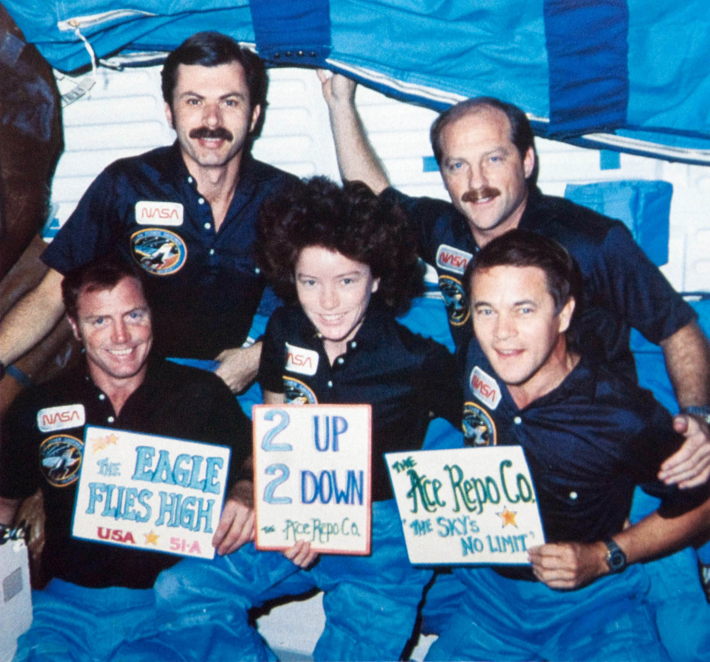 "The Discovery ""Eagle"" crew that pulled off the recovery operations in orbit.  Front, left to right:  Pilot Dave Walker with Mission Specialists Anne Fisher and joe Allen.  Back row:  Mission Specialist Dale Gardner and Mission 51-A Commander Frederick ""Rick"" Hauck."